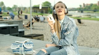 Beautiful girl in denim jacket listening music outdoors and singing