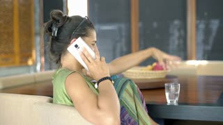 Beautiful tanned woman sitting in the dining room and chatting on cellphone