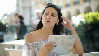 Beautiful woman cooling herself down with a map in the cafe, steadycam shot