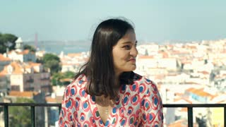 Beautiful woman feels free while standing on the balcony and smiling to the came