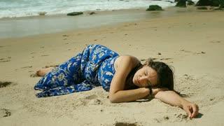 Beautiful woman lying on the sandy beach and sleeping