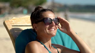 Beautiful woman relaxing on the sandy beach and smiling to the camera, steadycam