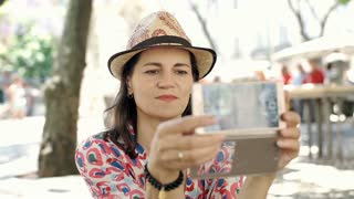 Beautiful woman sitting in the city and doing selfies on smartphone, steadycam s