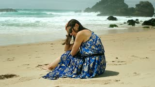 Beautiful woman sitting on the beach and crying