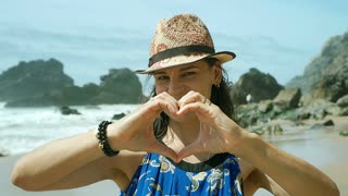 Beautiful woman smiling to the camera on the beach and doing heart from hands, s