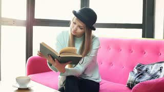 Blonde girl finishes reading book and yawning while sitting on the pink couch
