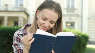 Blonde girl in checked shirt reading book in the park and smiling to the camera,