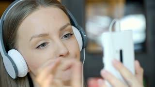 Bored girl listening music on headphones and browsing internet on smartphone