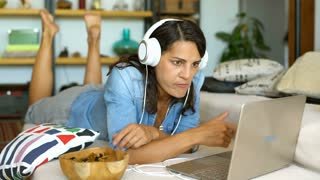 Bored woman looks unhappy while watching something on laptop and eating snacks