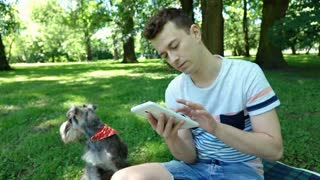 Boy checking tablet and receives good news while sitting in the park with his do