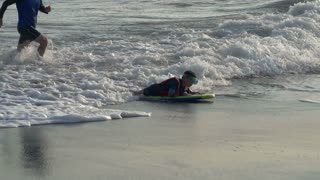Boy having fun on the sea with his father and skimboarding, steadycam shot, slow