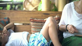 Boy lying on the wooden bench while his mother is reading menu, steadycam shot