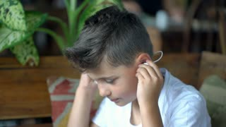 Boy puts on earphones to listen the music, steadycam shot