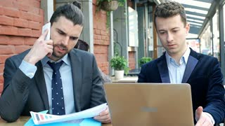 Businessman discuss papers while having a call and his colleague is working on l