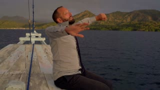 Businessman feels happy and free while sitting on the boat, steadycam shot, slow