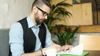Businessman looks angry while working on agreement in the cafe, steadycam shot
