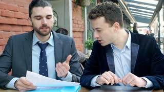 Businessman reading papers and asks his colleague to check information in the in
