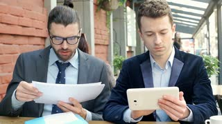 Businessman reading papers while his colleague is using tablet, steadycam shot