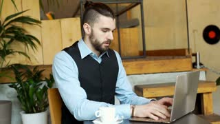 Businessman with bun working on notebook and receives good news, steadycam shot