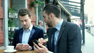 Businessmen talking with each other while using smartphones, steadycam shot