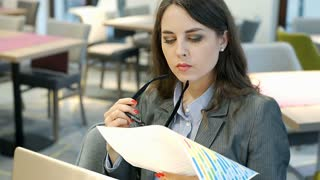 Businesswoman looking on papers and doing serious look to the camera in the cafe