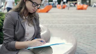 Businesswoman looks worried while working on papers in the city, steadycam shot