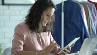 Businesswoman sitting by the desk and using tablet, steadycam shot