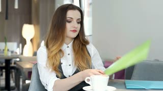 Businesswoman working in the cafe on papers and looks absorbed