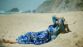 Calm woman in blue dress lying on the beach and relaxing