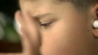 Close up of boy's face while listening music on earphones, steadycam shot