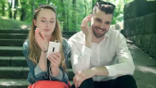 Couple listening music together and smiling to the camera in the park, steadycam