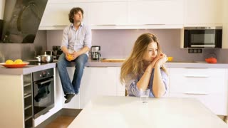Couple looking thoughtful and sitting in silence in the kitchen