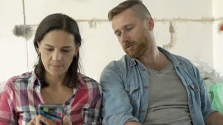 Couple looks worried while checking project of their new apartment, steadycam sh