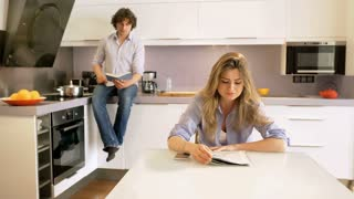 Couple reading publications in the kitchen and talking with each other
