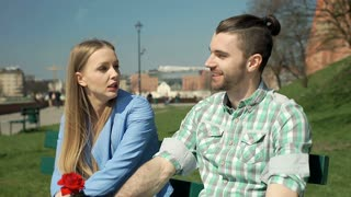 Couple sitting in the park and having an argument with each other, steadycam sho