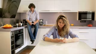 Couple sitting in the stylish kitchen and woman smiling to the camera