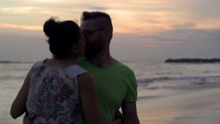Couple standing on the beach and kissing during sunset, steadycam shot, slow mot