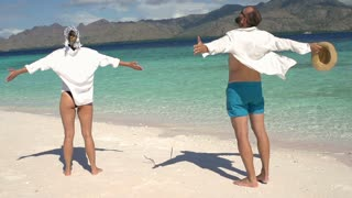 Couple standing on the beautiful beach and feel free, steadycam shot, slow motio
