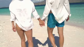 Couple walking on the beautiful beach and holding their hands, steadycam shot, s