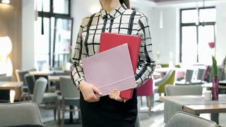 Elegant businesswoman holding folders with papers and standing in the cafe, stea