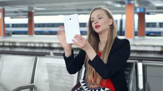 Elegant woman answers cellphone while using tablet on the train station, steadyc