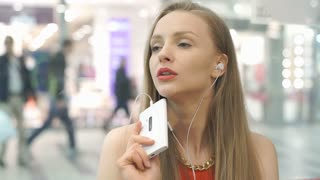 Elegant woman listening music and smiling to the camera in the cafe, steadycam s