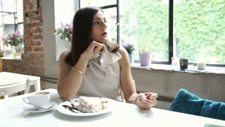 Elegant woman looks irritated while waiting for someone in the cafe, steadycam s