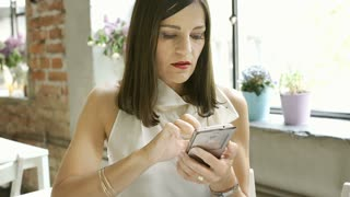 Elegant woman receives bad news on smartphone and looks worried, steadycam shot