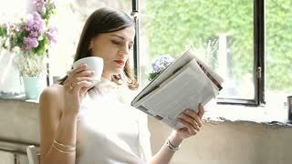 Elegant woman sitting by the window in the cafe and reading paper while drinking