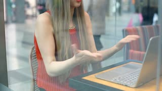 Elegant woman sitting in the cafe and quarrelling with someone on videochat, ste