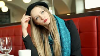 Elegant woman takes off bowler hat and scarf while sitting in posh restaurant