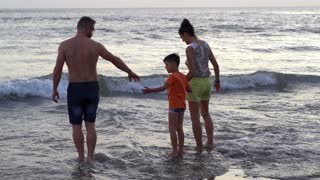 Family spending their holidays in the sea, steadycam shot, slow motion shot at 2