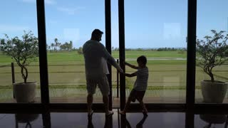 Father going outside with his son and jumping together, steadycam shot