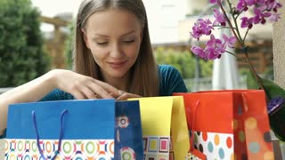 Girl checking her birthday presents and looks excited, steadycam shot